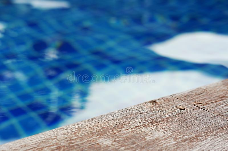 Empty rustic wooden table in front of blurred background of swimming pool. Perfect as summer themed product display stock photo