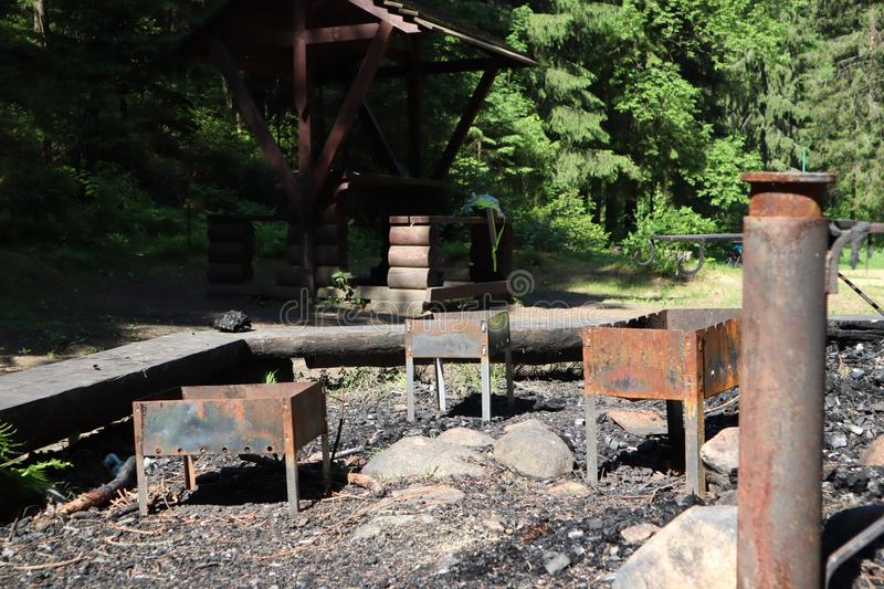 Empty rusty brazier for shish kebab in backgroun. Abandoned old brazier with coal in the woods. old barbecue grill in the forest.  royalty free stock photography