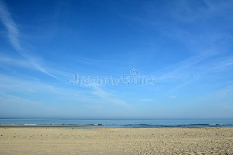 Empty beach and ocean with bright blue sky on a sunny summer day on island Texel in North Netherlands stock photography