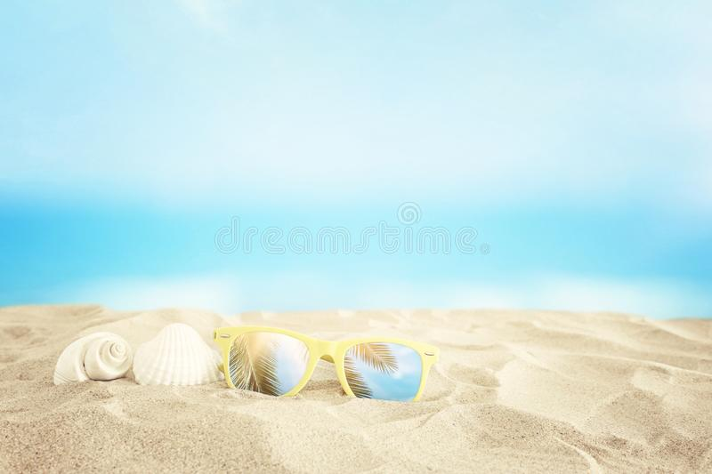 Empty sand beach, seashells and sunglasses in front of summer sea background with copy space.  stock photos