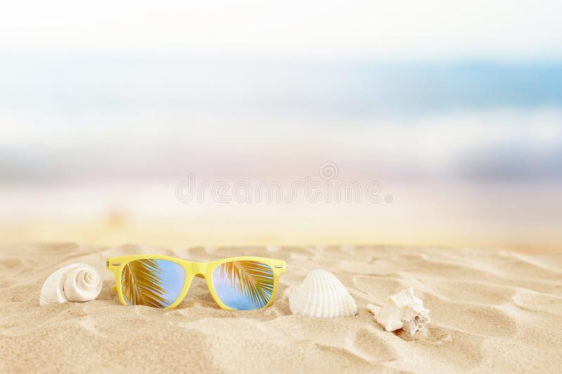 Empty sand beach, seashells and sunglasses in front of summer sea background with copy space.  stock images