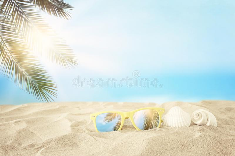 Empty sand beach, seashells and sunglasses in front of summer sea background with copy space.  royalty free stock photos