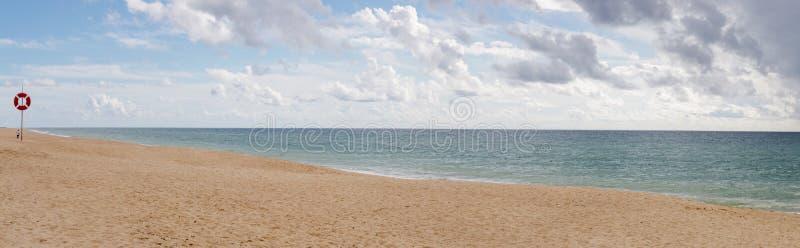 Empty sandy beach shoreline. Panorama of empty sandy beach shoreline on the Faro region, Portugal royalty free stock photography