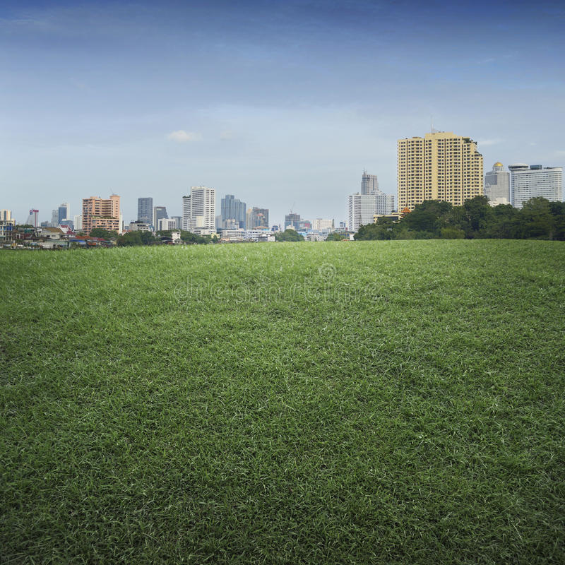 An empty scene of green grass field and office building city royalty free stock photo