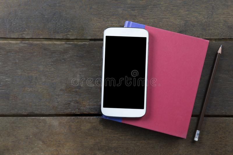 Empty screen mobile on red cover book and pencil on old wooden b. Ackground topview flatlay clippingpath at screen copyspace stock images