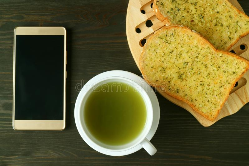 Empty Screen Smartphone with a cup of Hot Green Tea and Garlic Butter Toasts on Dark Color Background. Food texture antioxidants beige beverage black bread royalty free stock photos
