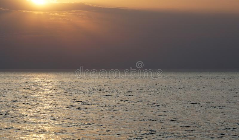 Empty sea to the horizon, evening. The sun is approaching the horizon, a light path is visible on the water. Suitable for the background composition stock photo