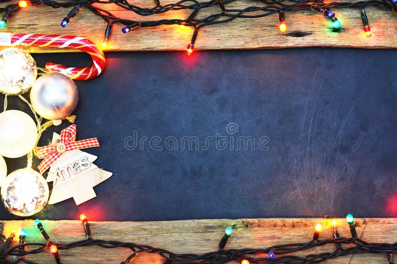 Empty seasonal background with glowing Christmas lights and decoration around blackboard. Empty seasonal background with glowing Christmas lights and decoration royalty free stock photos