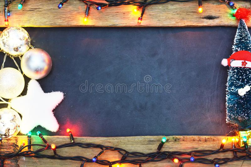 Empty seasonal background with glowing Christmas lights and decoration around blackboard. Empty seasonal background with glowing Christmas lights and decoration stock photos