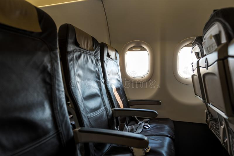 Empty seats and window inside an passenger aircraft. Summer travel concept.  stock photography