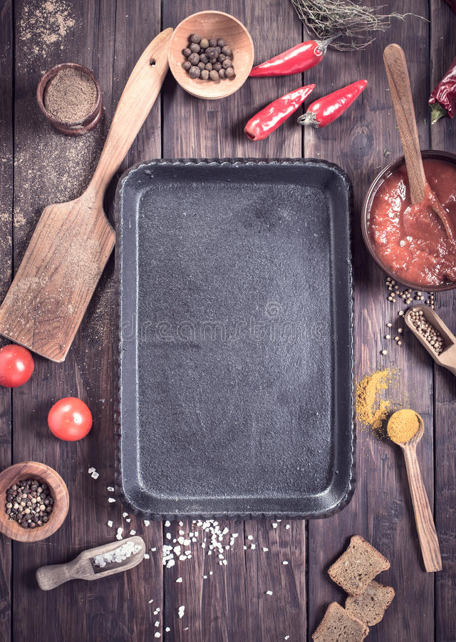Empty serving pan and various cooking ingredients. And spice among. Top view stock photos