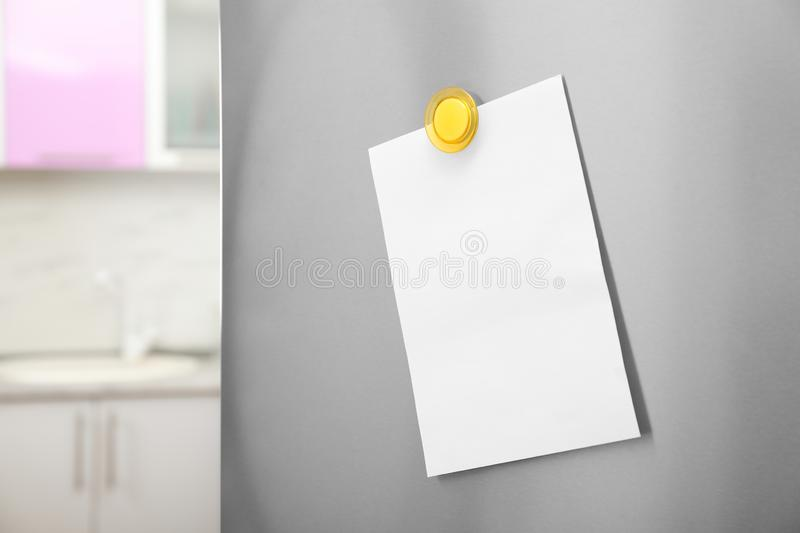 Empty sheet of paper with magnet on refrigerator door in kitchen. Space for text stock photos