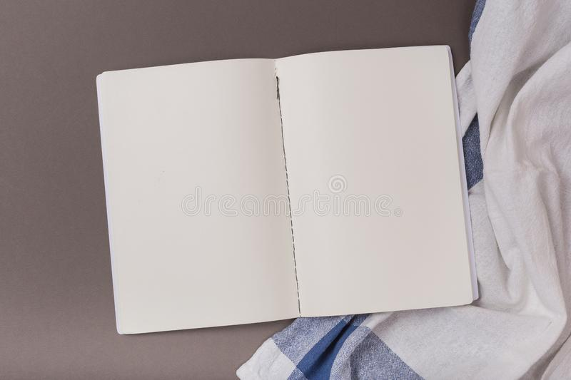 Empty sheets of open notebook and Towel on a grey background. Empty sheets of open notebook on a blue background and Towel Clean space stock images