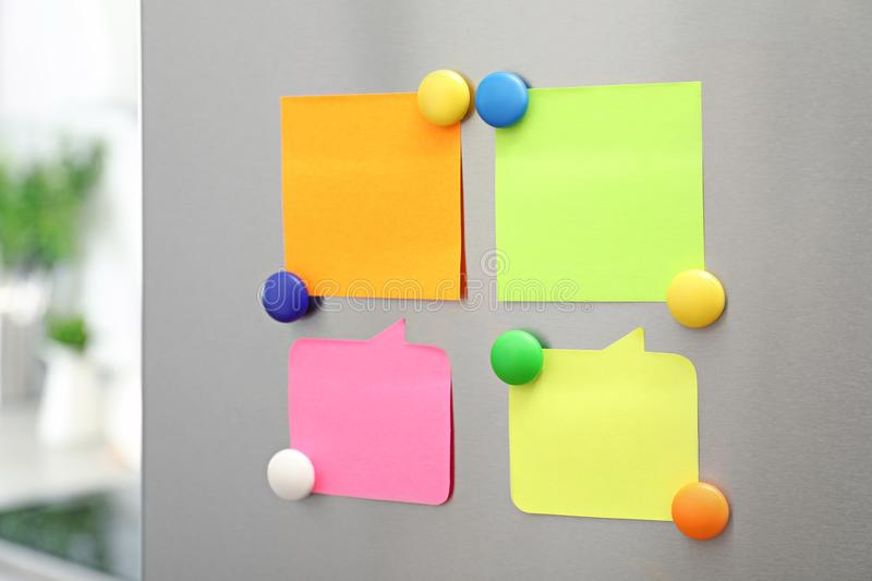 Empty sheets of paper with magnets on refrigerator door in kitchen. Space for text stock image