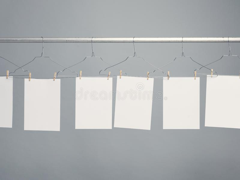 Empty sheets hanging in line. Empty sheets or pictures hanging with clothespin and hangers royalty free stock photos