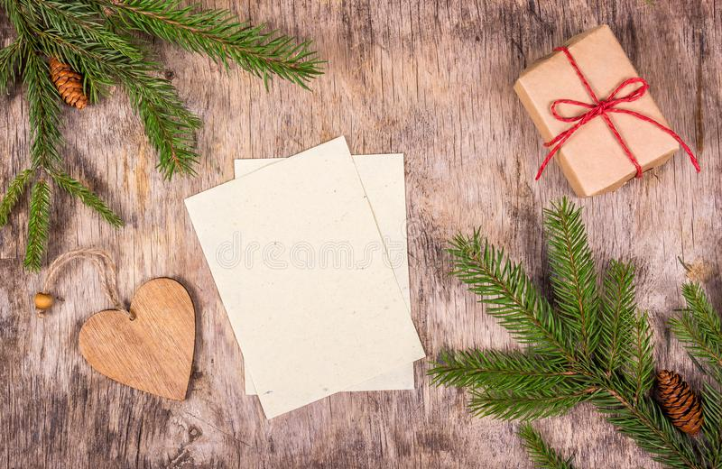 Empty sheets on wooden background. Christmas decorations with gift and fir tree. Preparing for Christmas, list of gifts. Copy space. Top view royalty free stock photography
