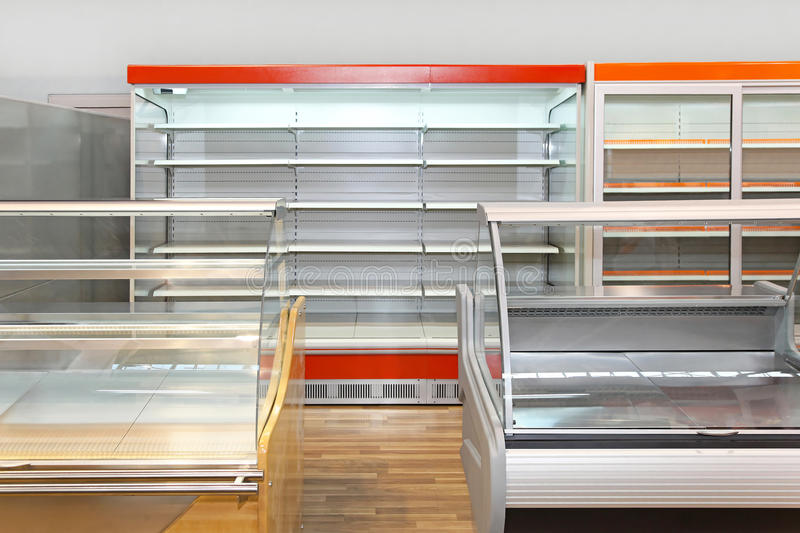 Empty shelves. Empty retail shelves and showcases in grocery store royalty free stock image
