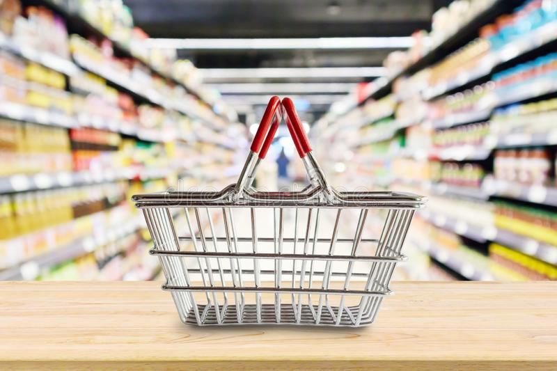 Empty Shopping basket on wood table over grocery store. Supermarket blur background stock photography
