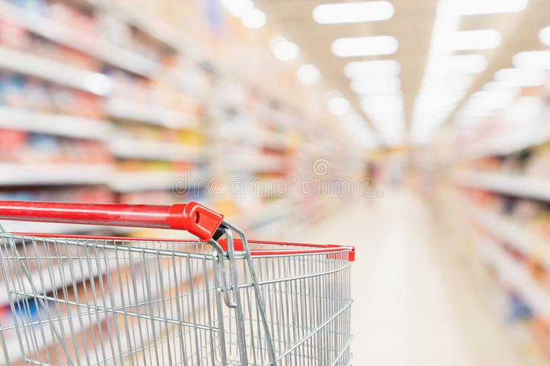 Empty shopping cart with abstract blur supermarket discount store aisle and product shelves interior. Defocused background royalty free stock image
