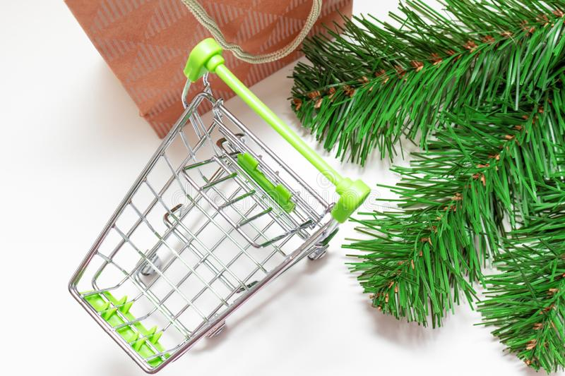 Empty shopping cart, trolley on white background with craft paper shopping bag and green decorated fir tree branches royalty free stock images
