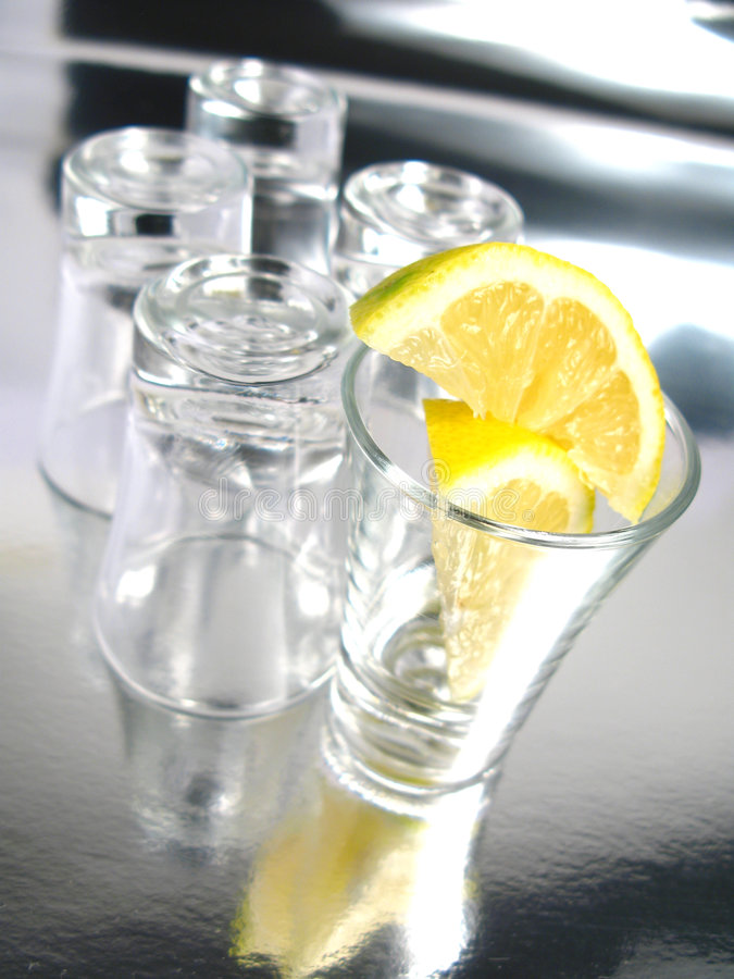 Empty shots with lemon. On a silver background royalty free stock image