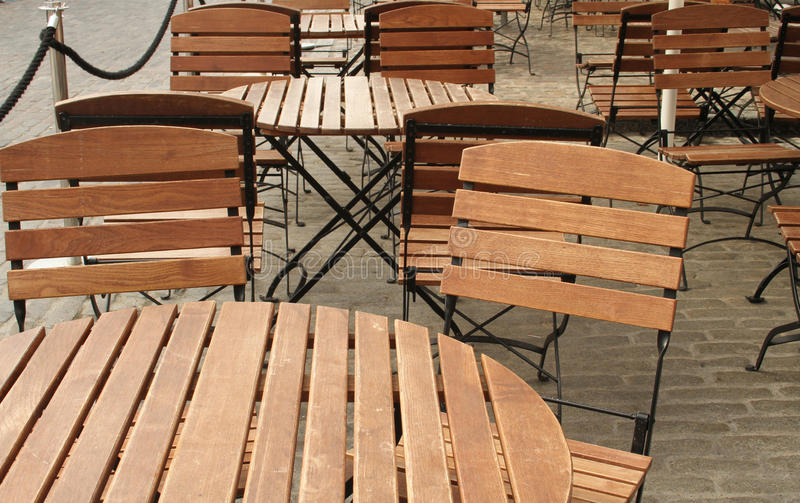 Empty sidewalk cafe. Empty wooden tables and chairs at a sidewalk cafe landscape orientation royalty free stock photo