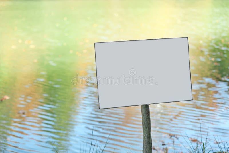 Empty sign board near pond stock photo