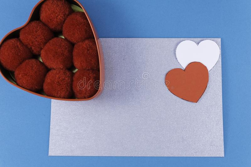 Empty silver letter with two hearts of red and white color box next to balls of cotton red on a blue background. Letter or invitation Minimalist concept Copy royalty free stock photo