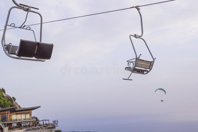 An empty ski lift on a sunny summer day. Skydiver in the sky.  royalty free stock photos