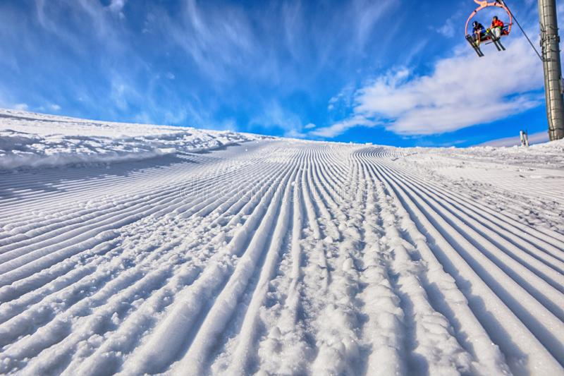Empty ski path in the ski resort after passing truck and people on the ski chairs. Sunny day. royalty free stock image