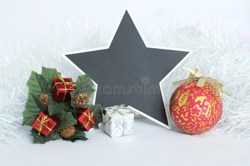 empty slate in the shape of a star to write a message with red and white gifts, green leaves, a fir tree crown and a red ball, stock photo