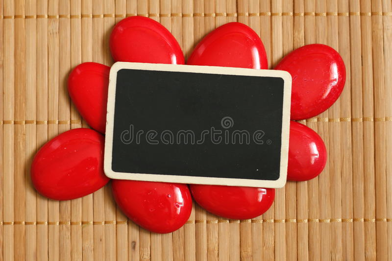 An empty slate to write a message surrounded by red pebble and bamboo floor royalty free stock photography