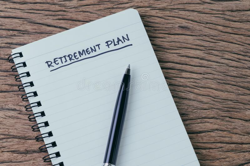 Empty small notepad with pen and handwriting headline as Retirement Plan on wood table in soft vintage tone, planning for saving stock photos
