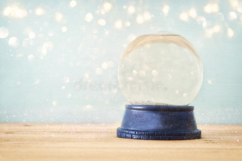 Empty Snow Globe over wooden table with glitter overlay. Magical Christmas concept. Copy space. Empty Snow Globe over wooden table with glitter overlay. Magical stock image