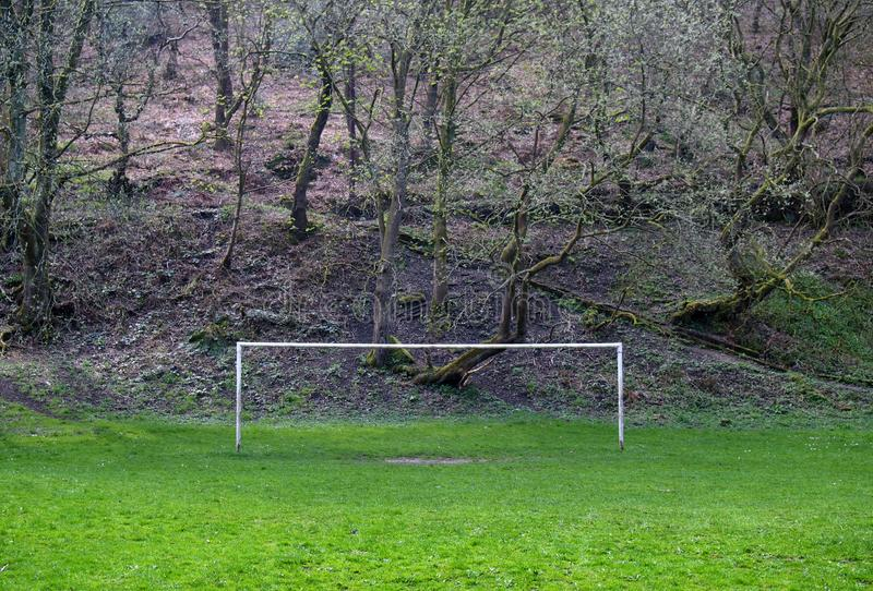 Empty soccer goalposts on a rural football pitch with a woodland hill in the background royalty free stock photography