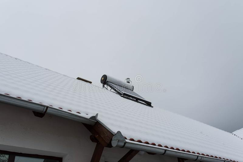 Empty solar water heater boiler on residentual house rooftop. At a cloudy cold winter day royalty free stock image