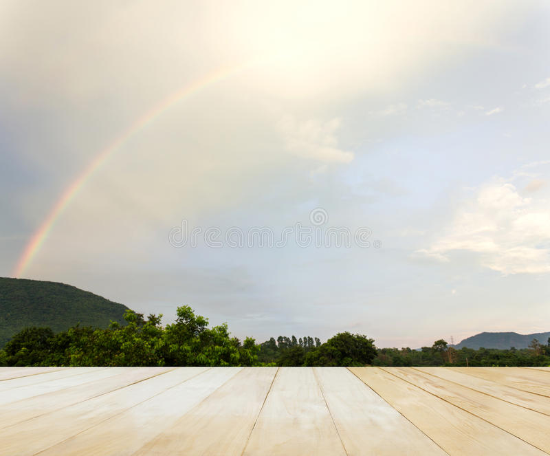 Empty space table top with mountain tree and rainbow on sky nature background royalty free stock photography