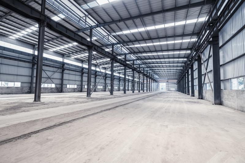 Empty steel structure warehouse. Empty steel structure workshop, abandoned factory buildings or warehouse royalty free stock photography