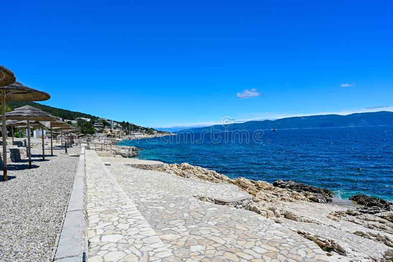 Empty stone beach with sunshades in Rabac Croatia. May 2019 stock photo