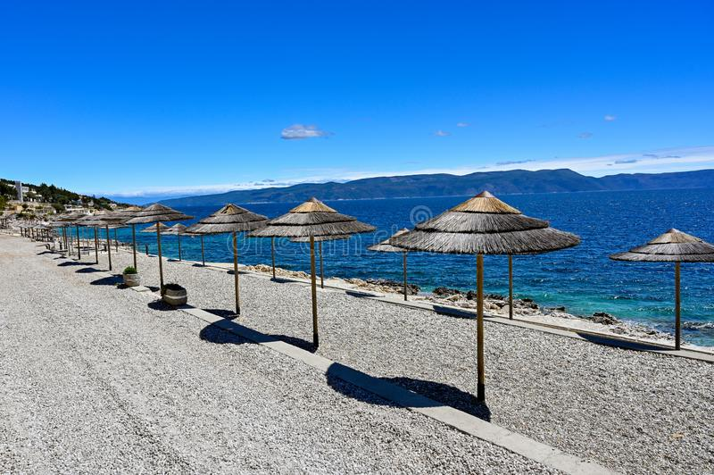 Empty stone beach with sunshades in Rabac Croatia. May 2019 stock images