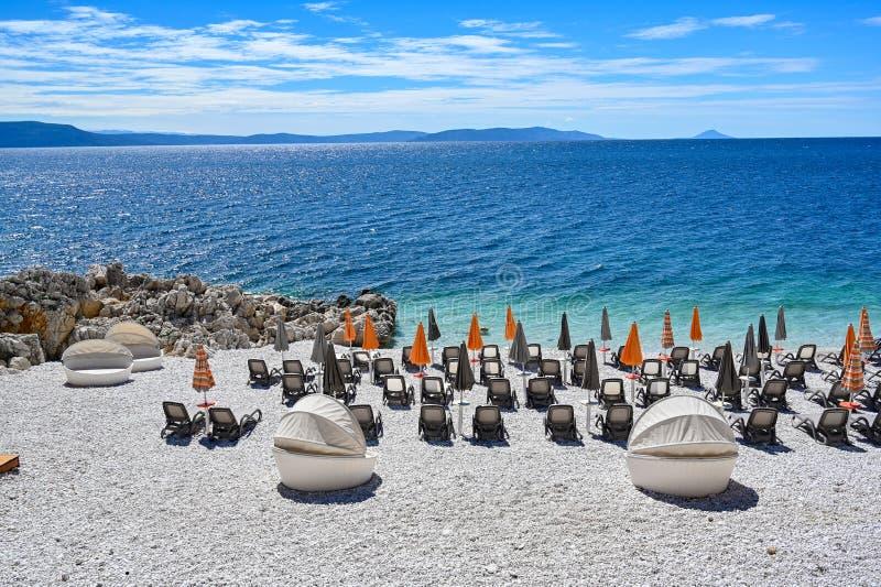 Empty stone beach with sunshades in Rabac Croatia. May 2019 stock photography