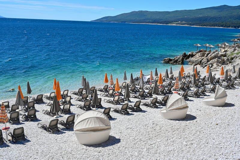 Empty stone beach with sunshades in Rabac Croatia. May 2019 royalty free stock image