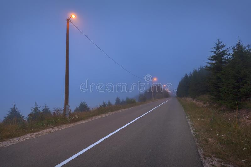 Empty straight road in mountain forest at spooky dusk stock photography