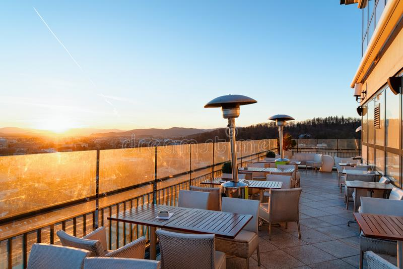 Empty street cafe with panoramic background in Ljubljana Slovenia sunset. Empty street cafe with tables and chairs with beautiful panoramic background on old stock photos