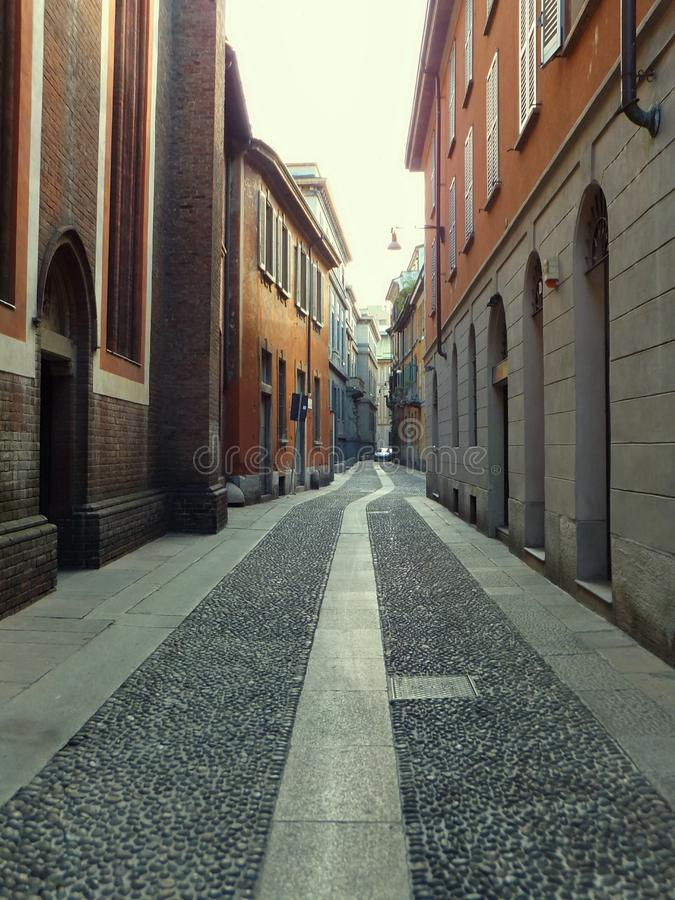 An empty street in Milan, Italy, lined with a church and old houses, its cobblestones leading into distance. An empty street in Milan, Italy, lined with a church stock photos