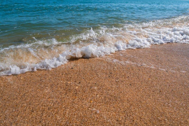 Empty summer beach with golden sand and azure water. Empty summer beach with golden sand and azure splashing water stock photos