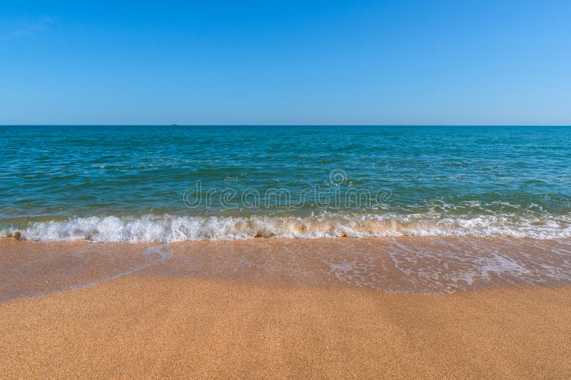 Empty summer beach with golden sand and azure water. Empty summer beach with golden sand and azure splashing water royalty free stock photography