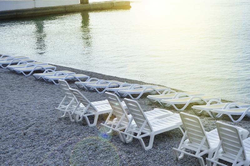 Empty sun loungers by the sea early in the morning, calm, sunrise. Summer, beach, nature, coast, pebble, water, background, glare, travel, vacation, white stock photo