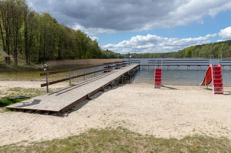 Empty swimming pool in Central Europe. Wooden jetty on the lake royalty free stock image