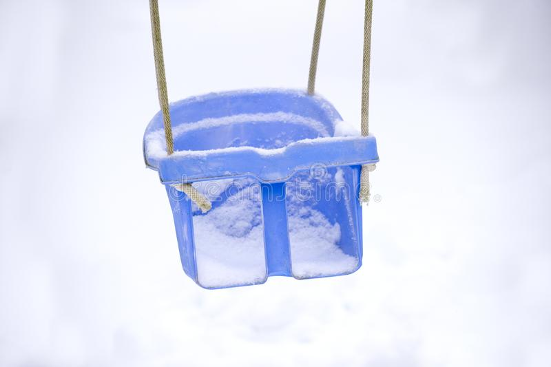 Empty swing in winter time with snow royalty free stock images